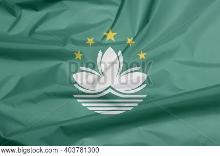 Fabric Flag Of Macau. Crease Of Macau Flag Background, Green With A Lotus And Stylised Governor Nobr