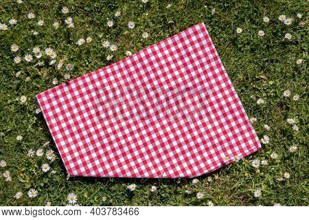 Red Picnic Tablecloth. Red Checkered Picnic Blanket On A Meadow With Daisies In Bloom. Beautiful Bac