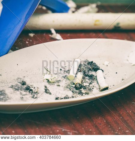 Cigarette Butts In A White Plate Ashtray