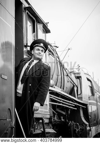 European Or American Train Conductor Is On His Duty On A Platform And Other Trains. Railway, Steam T
