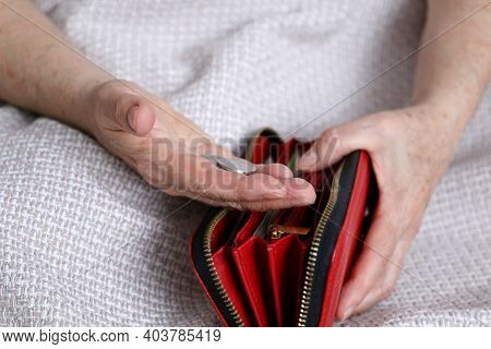 Elderly Woman Takes Out A Coins From Her Wallet, Wrinkled Female Hands Closeup. Concept Of Poverty,