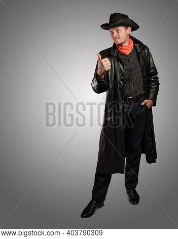 Cowboy In Leather Clothing Points To The Side. Unshaven Smiling Man In A Hat And Cloak. Macho Guy On
