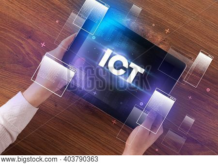Close-up of a hand holding tablet with ICT abbreviation, modern technology concept