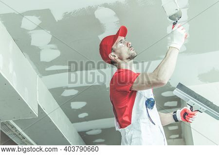 Construction And Remodeling Worker In His 30s Wearing Red Uniform Patching Drywall Ceiling Inside Re