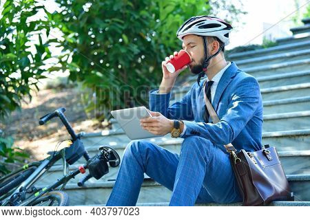Businessman Sitting On Stairs With Digital Tablet And Drinking Coffee. Business And Alternative Tran