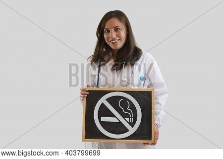 Smiling Female Doctor Holding Blackboard With Ban On Smoking. Stop Smoking Concept. Isolated On Grey