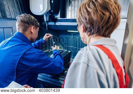 Supervisor woman watching young worker changing setup of lathe machine
