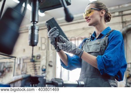 Woman in metal workshop checking workpiece for accuracy