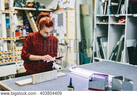 Woman glazier worker sticking together glass panes with ultraviolet lamp. Industry, manual work