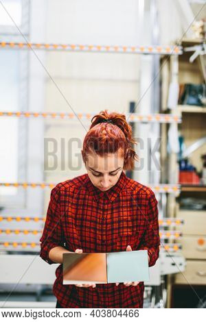 Woman glazier worker sticking together glass panes. Industry, manual work