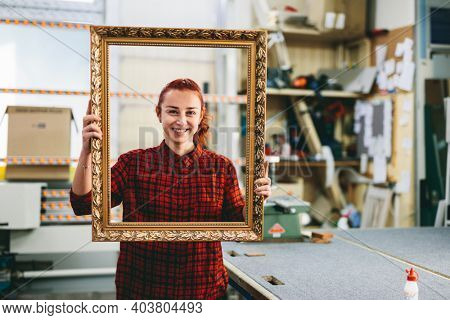 Woman worker portrait after doing a wooden frame renovation and refurbishment. Industry, manual work