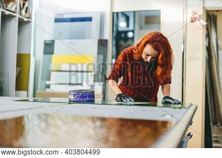 Glazier woman worker polishing glass in workshop. Industry and manufactory production