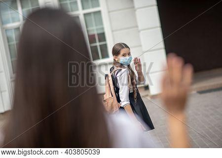Masked Schoolgirl Saying Goodbye To Mom Near School
