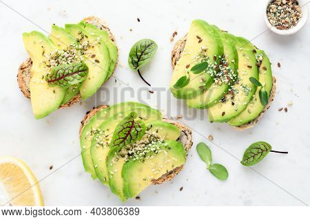 Avocado Slices With Seeds And Micro Greens On Toasted Bread On White Background. Healthy Vegan Veget
