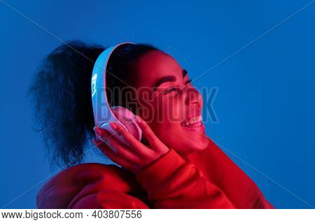 Happiness. African-american Womans Portrait On Blue Background In Red-pink Neon Light. Listening To