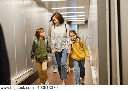 Happy mother walking along the airport terminal together with her children for boarding they going for vacation