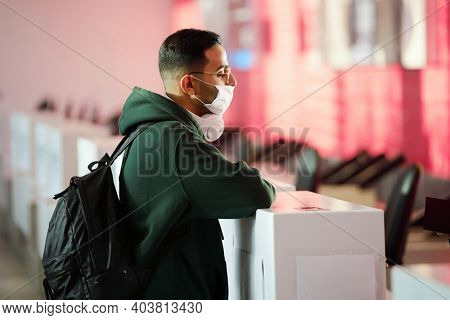 Young man in protective mask standing at the registration desk at the airport