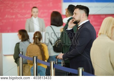 Young businessman in suit talking on mobile phone while standing in a queue and waiting for his registration