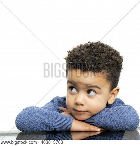 Close Up Portrait Of Little Afro American Boy Resting On Arms At Table. Kid Looking Aside Isolated O