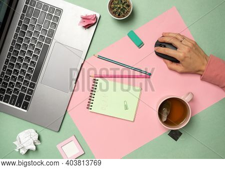 Office Desk Top View. Workplace With Girls Hands, Laptop, Cup Of Tea, Cactus, Notepad. The Girl Work