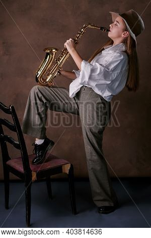 Girl Plays Jazz Saxophone. Talented Child Artist Musician In A Hat, Shirt And Trousers