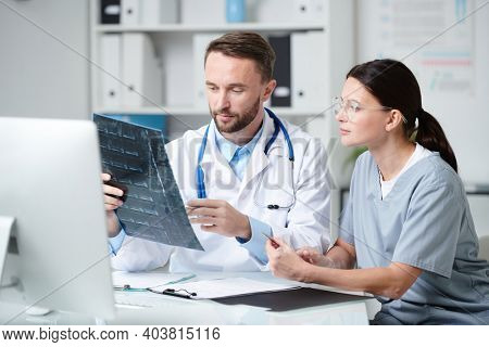 Two young clinicians in uniform sitting by desk in front of computer monitor, discussing x-ray of patient and consulting in medical office