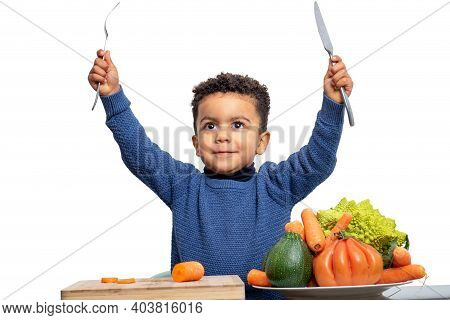 Close Up Fun Portrait Of Cute Afro American Kid Raising Knife And Fork With Vegetables On Table. Boy