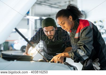 Young bearded man in workwear holding lamp and bending over open hood while his female colleague pointing at car engine during work