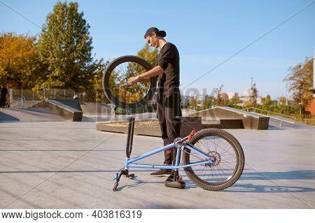 Young male bmx biker adjusts his bike in skatepark