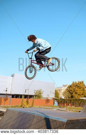 Male bmx biker doing trick on ramp in skatepark