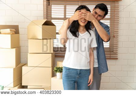 Smiling Young Asian Happy Couple Close Girlfriend Eyes For A Surprise At Moving Day In Their New Hom