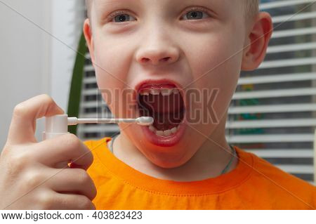The Boy Squirts Medicine Into His Mouth For A Sore Throat.