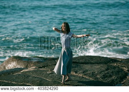 The young dancers woman is engaged in choreography on the ocean coast.