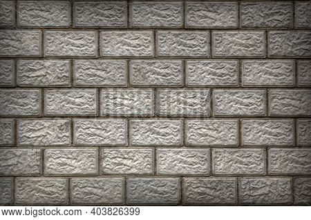 The Wall Of The House Is Made Of Gray Concrete Blocks. Aged Background Or Wallpaper With Vignetting.