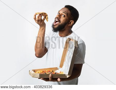 Bearded Black Guy Eating Slice Of Pizza Standing Posing With Large Pizzeria Box Over White Studio Ba