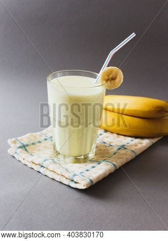 Yummy Banana Milkshake In Glass On Gray Background