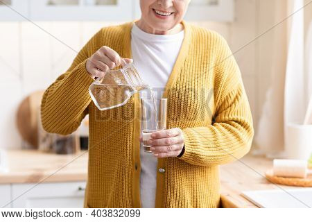 Hydration, Water Drinking Concept. Closeup Of Unrecognizable Grandmother Pouring Water Into Glass, K