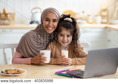Happy Muslim Mom And Daughter Having Snacks And Drinks In Kitchen, Happy Islamic Lady In Hijab Enjoy
