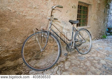 View Of Forgotten Old Bike Parked Against The Wall In One Of The Empty Stone Streets Of An Abandoned