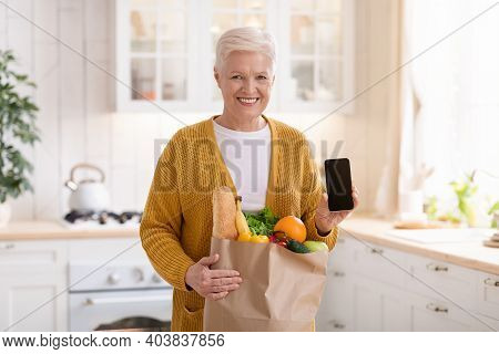 Cheerful Senior Woman With Shopping Bag Full Of Grocery Showing Smartphone With Blank Screen, Kitche