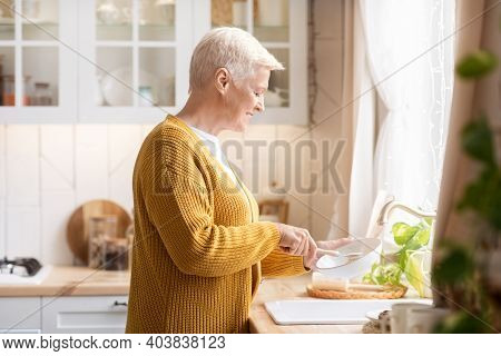 Side View Of Happy Senior Woman With Short Haircut Washing Dishes In Kitchen, Empty Space. Positive
