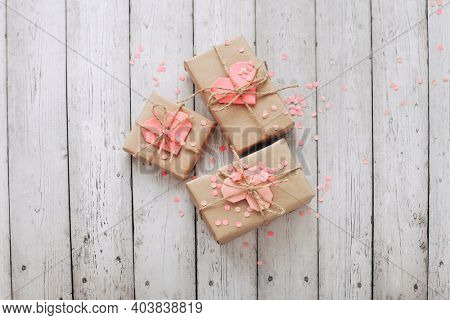 Happy Valentine's Day photography with gift boxes and paper origami heart on wooden background. Romantic greeting card.
