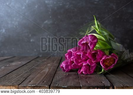 Bouquet Of Fresh Purple Tulips On Dark Vintage Planks In Front Of Gray Concrete Wall. Atmospheric Ba