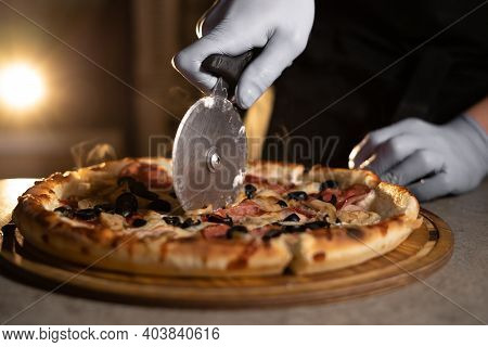Hot Pizza With Cheese Is Cut By Hand By A Chef Wearing A Rubber Glove With A Special Knife. Ready Ba