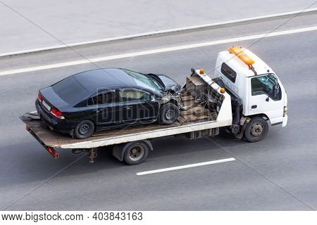 Wrecked Car After An Accident On A Tow Truck Transported On A Highway