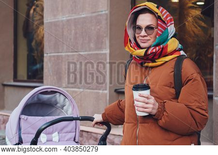 Fashionable Modern Mom With A Stroller On A Walk In The City, Autumn. Mom Drives A Stroller Through