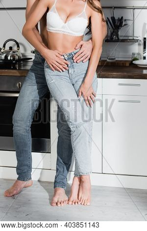 Cropped View Of Man In Jeans Hugging Sensual Woman In Bra And Jeans In Kitchen