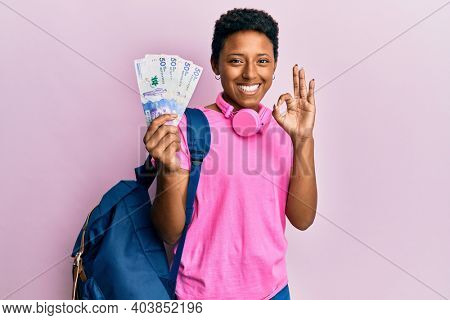 Young african american girl wearing student backpack holding colombian pesos banknotes doing ok sign with fingers, smiling friendly gesturing excellent symbol
