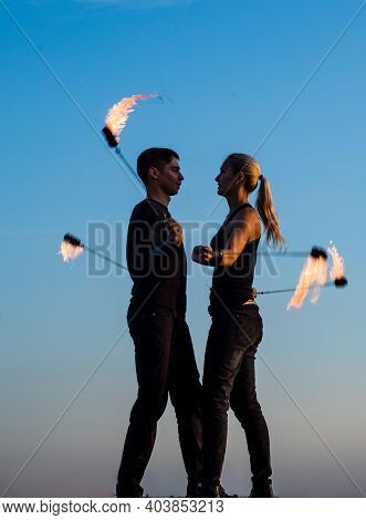 Sexy Couple Of Fire Dancers Spin Flaming Poi On Idyllic Evening Blue Sky Outdoors, Motion