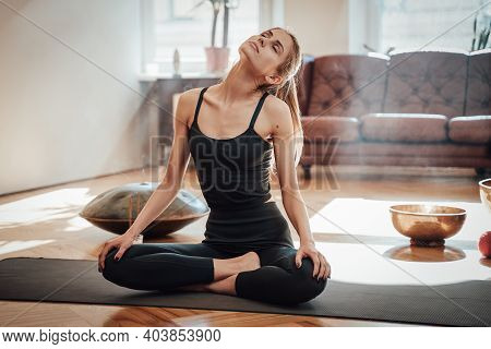 Relaxed Woman With Brown Hairs Works Out Doing Yoga On Mat In Living Room With Simple Design And Mod